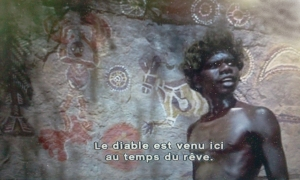 Le jeune aborigène explique sa peinture pariétale du pays du rêve